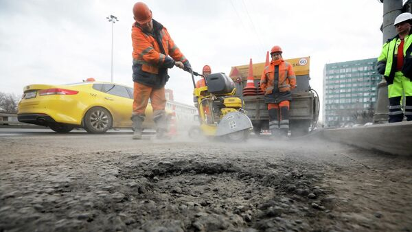 Рабочие проводят латочный ремонт дорожного покрытия