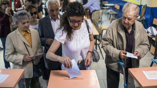 Избиратели голосуют на одном из избирательных участков в Мадриде в заключительный день голосования на выборах в Европейский парламент. 26 мая 2019