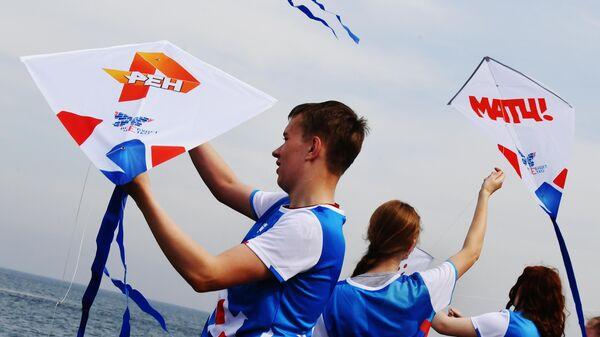Участники акции запускают воздушных цифровых змеев с логотипами телеканалов во Владивостоке