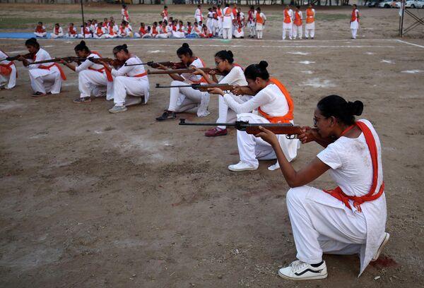 Члены Durga Vahini, националистической организации Вишва хинду паришад демонстрируют свои навыки самообороны с огнестрельным оружием