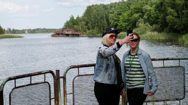 Туристы делают селфи в речном порту заброшенного города Припять, недалеко от Чернобыльской АЭС, Украина
