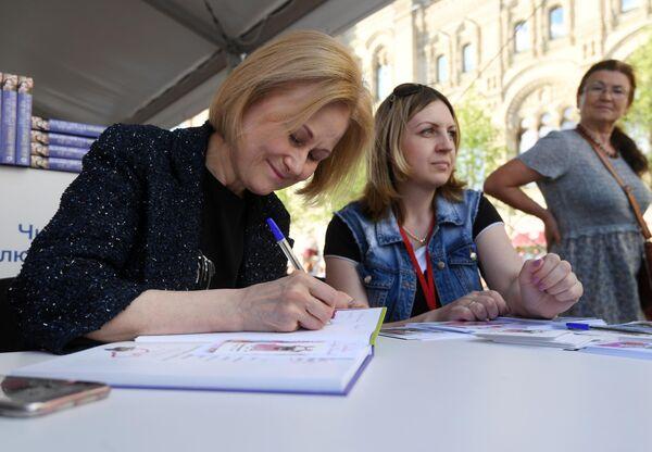 Писательница Дарья Донцова дает автографы во время ежегодного российского книжного фестиваля на Красной площади