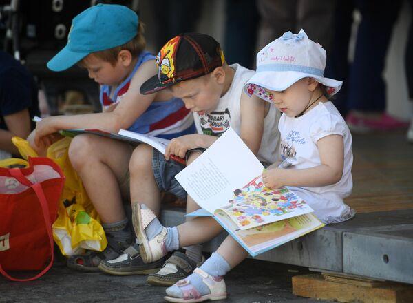 Юные читатели с книгами на ежегодном российском книжном фестивале на Красной площади