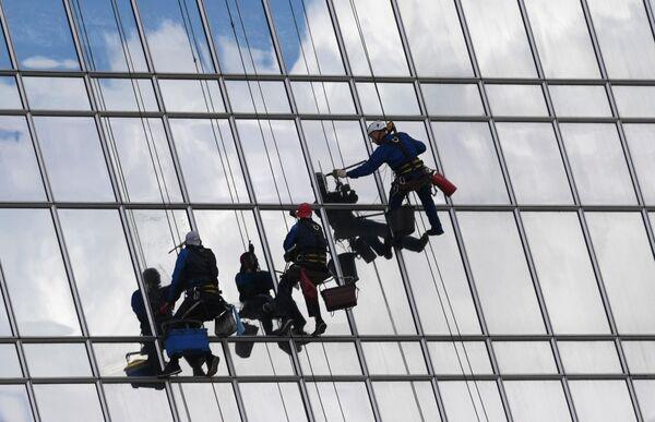Промышленные альпинисты моют фасад высотного здания в Москве