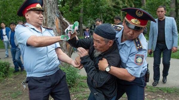 Сотрудники полиции задерживают участника несанкционированного митинга  в день проведения выборов президента Казахстана в Алма-Ате