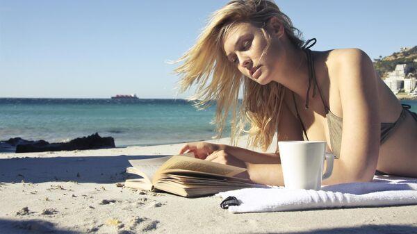 Девушка читает на пляже
