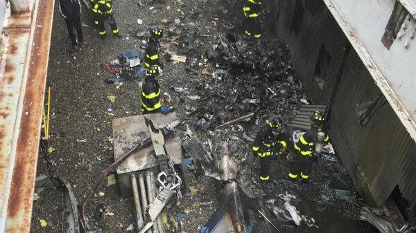 Пожарные службы среди обломков крыши от столкновения вертолета со зданием в Нью-Йорке. 10 июня 2019