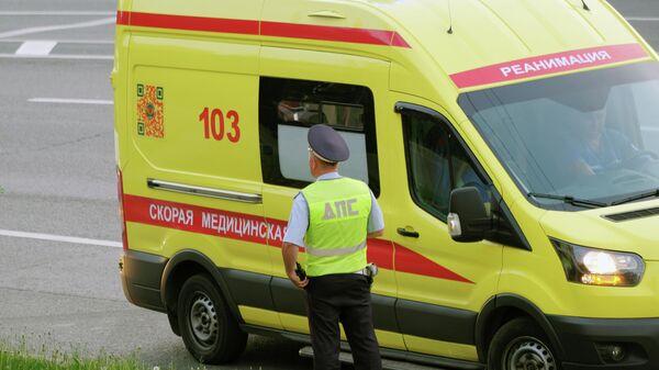 Сотрудник Дорожно-патрульной службы ГИБДД и автомобиль скорой медицинской помощи
