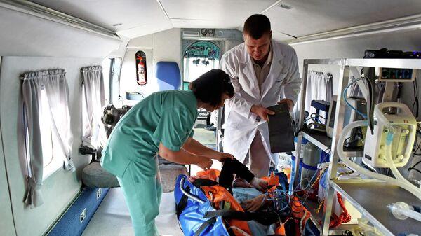 Сотрудники медицинской службы с пациентом на борту санитарного вертолета