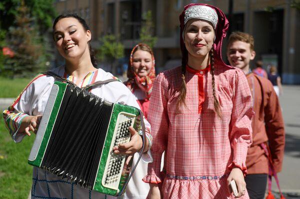 Молодые люди в национальных костюмах на Параде дружбы народов в парке им. М. Горького в Казани