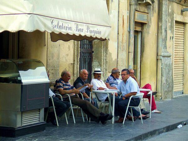 Мужчины общаются в кафе