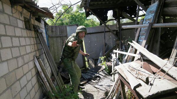 Военнослужащий ДНР во дворе дома пострадавшего в результате обстрела
