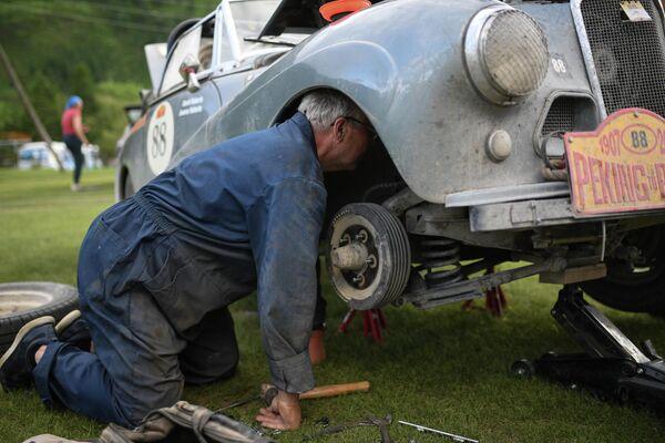 Участник международного ралли на старинных автомобилях Пекин - Париж 2019 на месте ночной стоянки возле села Чибит в Республике Алтай ремонтирует свой автомобиль Sunbeam Alpine (1954 г.)