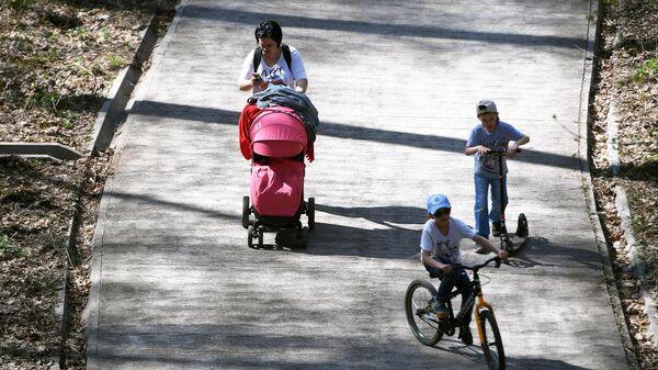 Женщина гуляет с детьми в парке