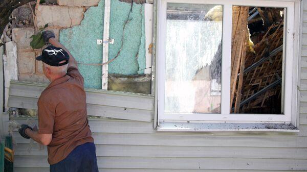 Мужчина устраняет повреждения жилого дома в Донецке, пострадавшего в результате обстрела