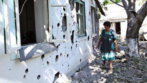 Женщина у жилого дома в поселке Новая Марьевка в Донецкой области, пострадавшего в результате ночного обстрела. 9 июня 2019