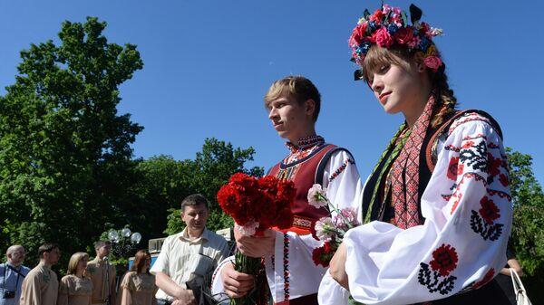 Горожане в национальных костюмах возлагают цветы к памятнику поэта Тараса Шевченко
