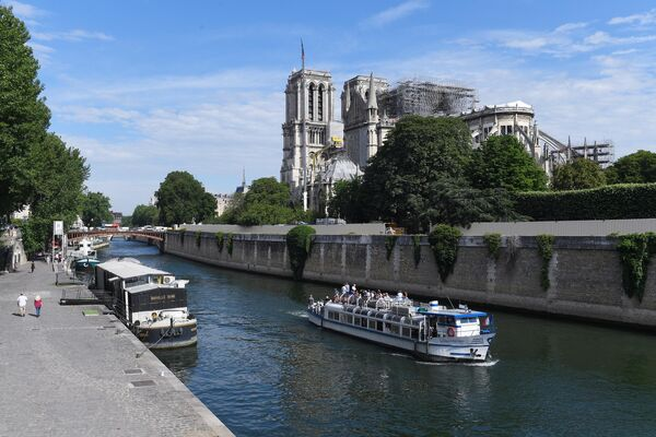 Прогулочный катер Le Martin Pêcheur (справа) на Сене вблизи Собора Парижской Богоматери (Notre Dame de Paris) в Париже