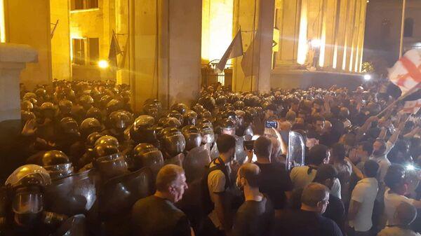 Сотрудники полиции и участники акции протеста у здания парламента Грузии в Тбилиси