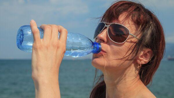 Девушка пьет из пластиковой бутылки