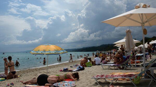 Отдыхающие на пляже полуострова Халкидики в Греции