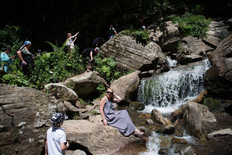 Туристы в природном парке водопадов Менделиха на горнолыжном курорте Роза Хутор в Сочи