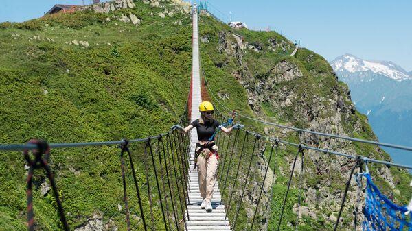 Девушка идет по подвесному пешеходному мосту над ущельем на горнолыжном курорте Роза Хутор в Сочи