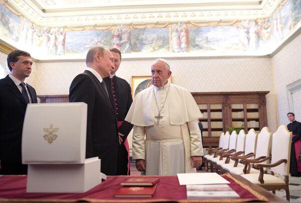 Президент РФ Владимир Путин и Папа Римский Франциск во время обмена подарками в Апостольской библиотеке в Ватикане