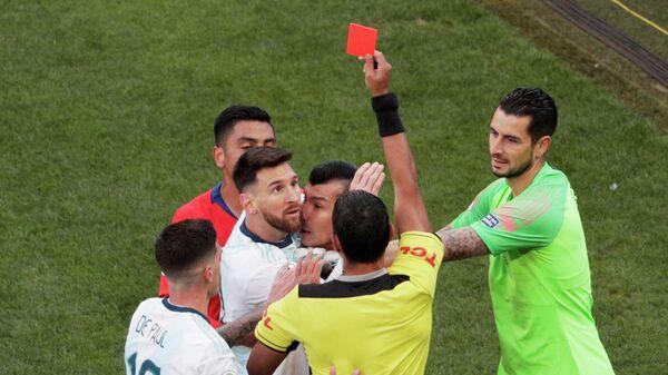 Капитан сборной Аргентины Лионель Месси (второй слева) получает красную карточку