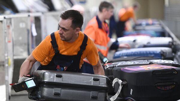 Сотрудник багажной службы во время работы в международном аэропорту Шереметьево в Москве. Архивное фото