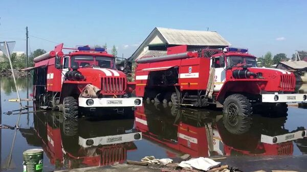Автомобили противопожарной службы МЧС РФ откачивают воду в районе подтопления в городе Тулун Иркутской области. 10 июля 2019