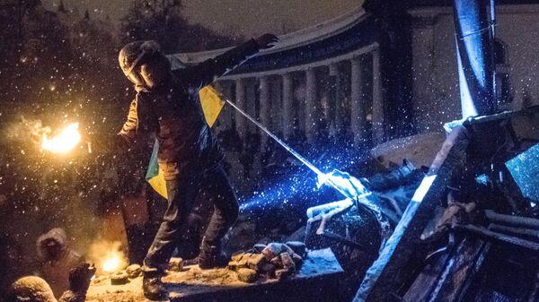 Участник акции протеста кидает бутылку с зажигательно смесью в полицейских на улице Грушевского в Киеве