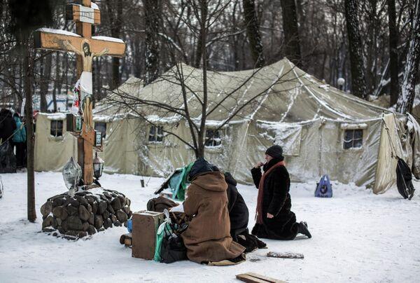Верующие молятся в палаточном лагере сторонников Партии Регионов в Мариинском парке Киева