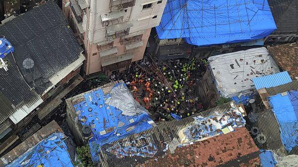 Спасатели и жители ищут выживших на месте рухнувшего здания в Мумбаи, Индия. 16 июля 2019