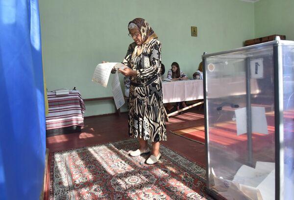 Женщина  голосует на досрочных выборах в Верховную раду Украины на избирательном участке в селе Фийна Львовской области