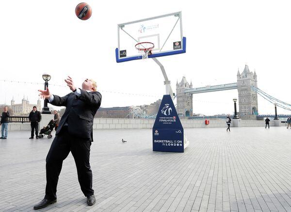 Мэр Лондона Борис Джонсон забивает мяч в корзину в Лондоне. 8 апреля 2013 года
