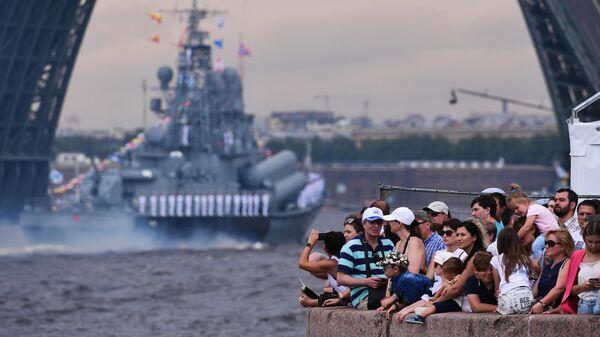 Зрители наблюдают за проходом кораблей по Неве на главном военно-морском параде, посвященном Дню ВМФ в Санкт-Петербурге