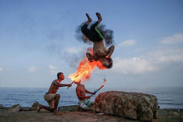 Палестинцы показывают трюк с огнем на пляже в городе Газа