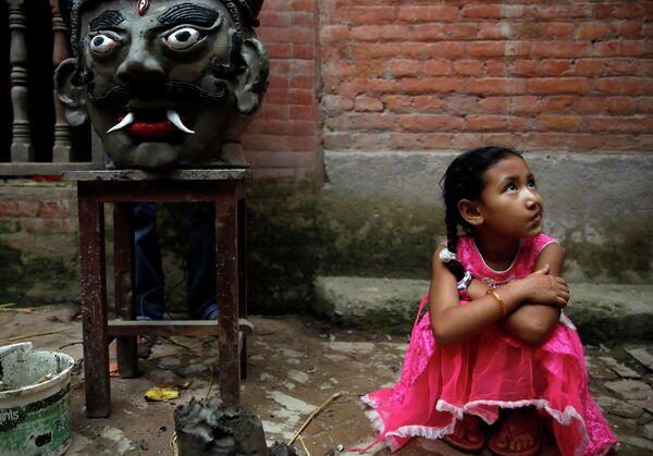 Девочка сидит рядом с чучелом демона Гхантакарна в Бхактапуре, Непал