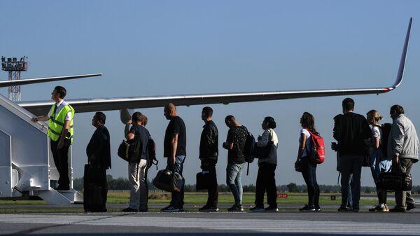Пассажиры перед посадкой в самолет