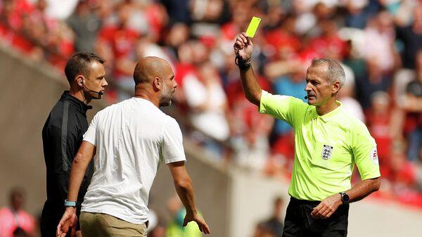 Главный тренер Манчестер Сити Хосеп Гвардиола (в центре) и английский арбитр Мартин Аткинсон (справа)