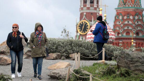Жители Москвы, одетые в теплые осенние куртки, в парке Зарядье