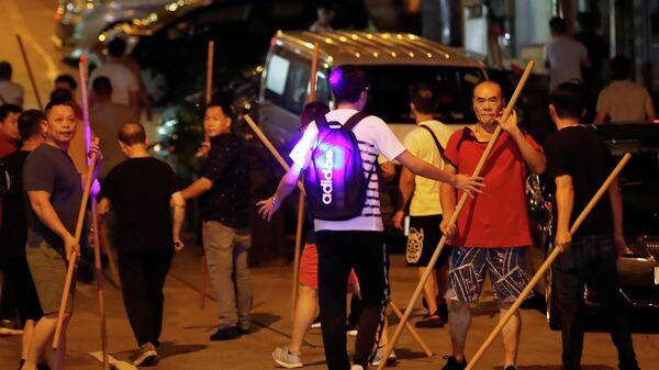 Группа людей с прутами, пытается напасть на антиправительственную демонстрацию в Гонконге. 5 августа 2019