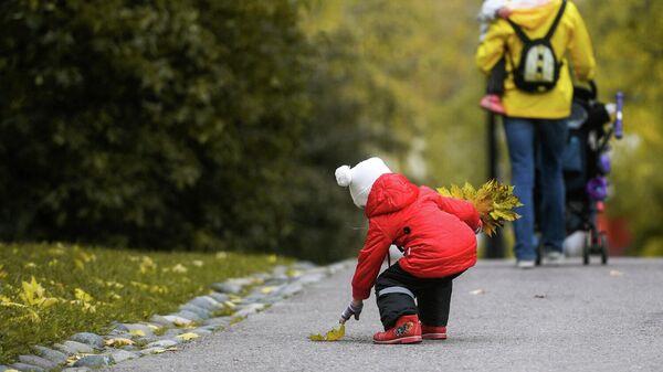 Ребенок собирает осенние листья в парке