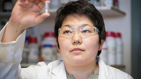 Асель Сартбаева держит в руках пробирку с экспериментальной вечной вакциной от туберкулеза