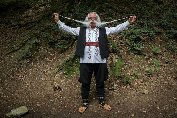 70-летний пенсионер Зоран Лазаревич показывает усы, которые отрастил для регионального фестиваля бородачей в Сербии