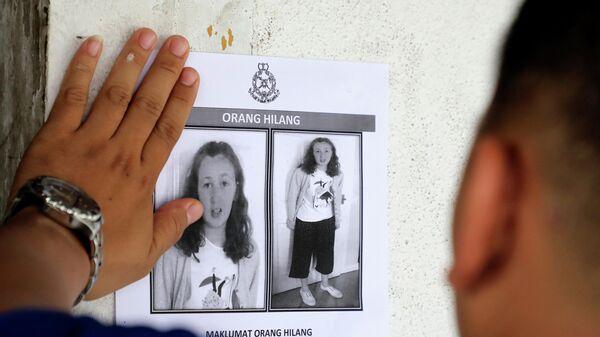Полицейский приклеивает фотографию 15-летней ирландской туристки Норы Куоирин, которая пропала без вести на курорте в Малайзии