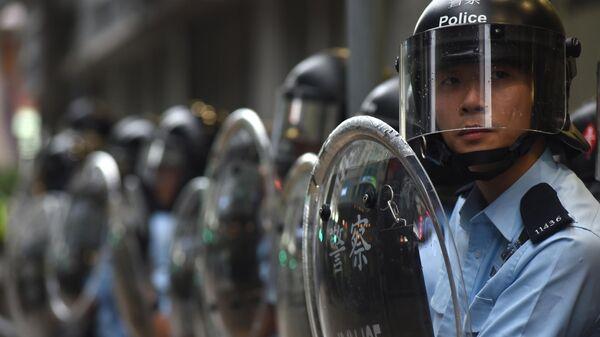 Полицейские у полицейского участка во время акции протеста в Гонконге