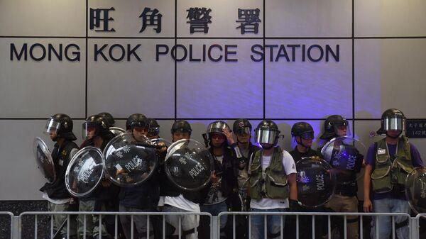 Полицейские у полицейского участка во время акции протеста оппозиционеров в Гонконге