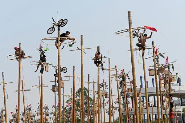 Участники поднимаются на столбы во время Panjat Pinang на пляже в Джакарте